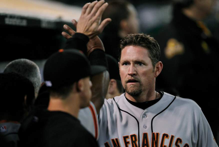 San Francisco Giants baserunner Aubrey Huff is congratulated after scoring a run during the fourth inning of his MLB pre-season baseball game against the Oakland Athletics in Oakland, California, April 3, 2012. REUTERS/Beck Diefenbach