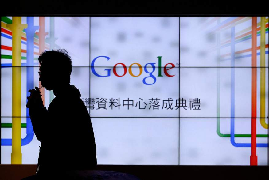 A man walks past a TV wall during a media tour at the Google data centre in Changhua Coastal Industrial Park, central Taiwan, December 11, 2013. REUTERS/Pichi Chuang