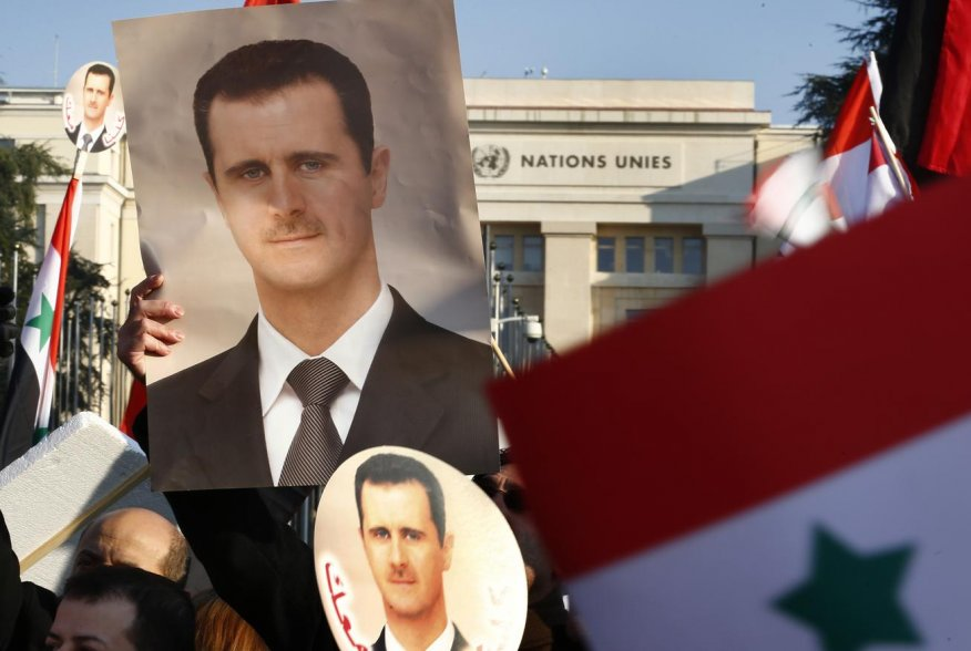 Supporters of Syrian President Bashar al-Assad carry Syrian flags and portraits in front of the United Nations European headquarters in Geneva January 31, 2014. REUTERS/Denis Balibouse