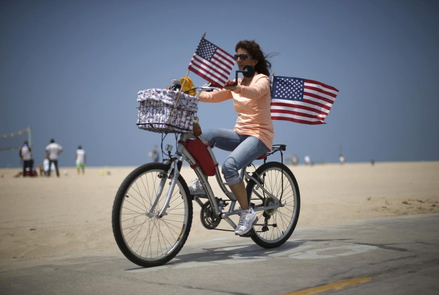A woman cycles with U.S. flags on Independence Day on Venice Beach in Los Angeles, California July 4, 2014. The holiday marks the signing of the Declaration of independence from the British on July 4, 1776. REUTERS/Lucy Nicholson