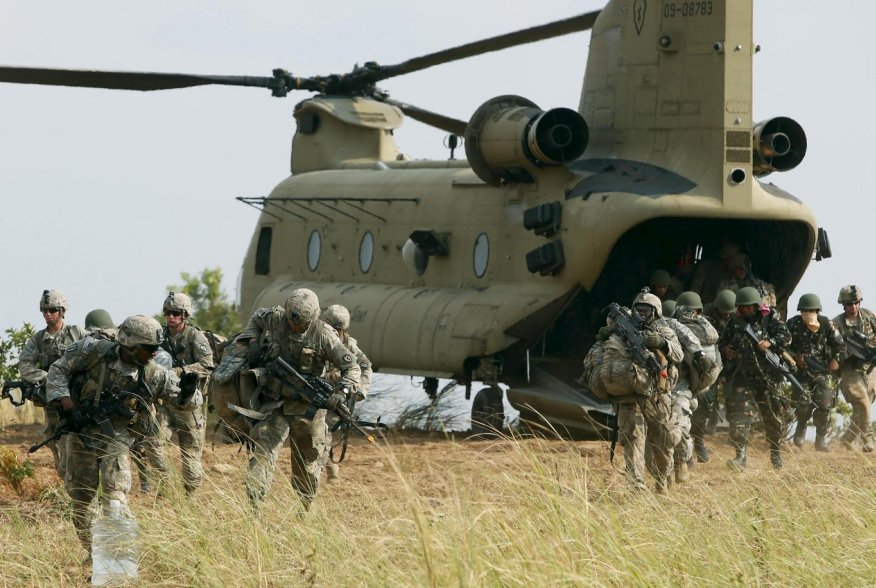 "U.S. soldiers of 2nd Stryker Brigade Combat Team disembark from a U.S. military helicopter CH-47 as they take part in the annual ""Balikatan"" (shoulder-to-shoulder) war games with Filipino soldiers at a military camp, Fort Magsaysay, Nueva Ecija in norther"