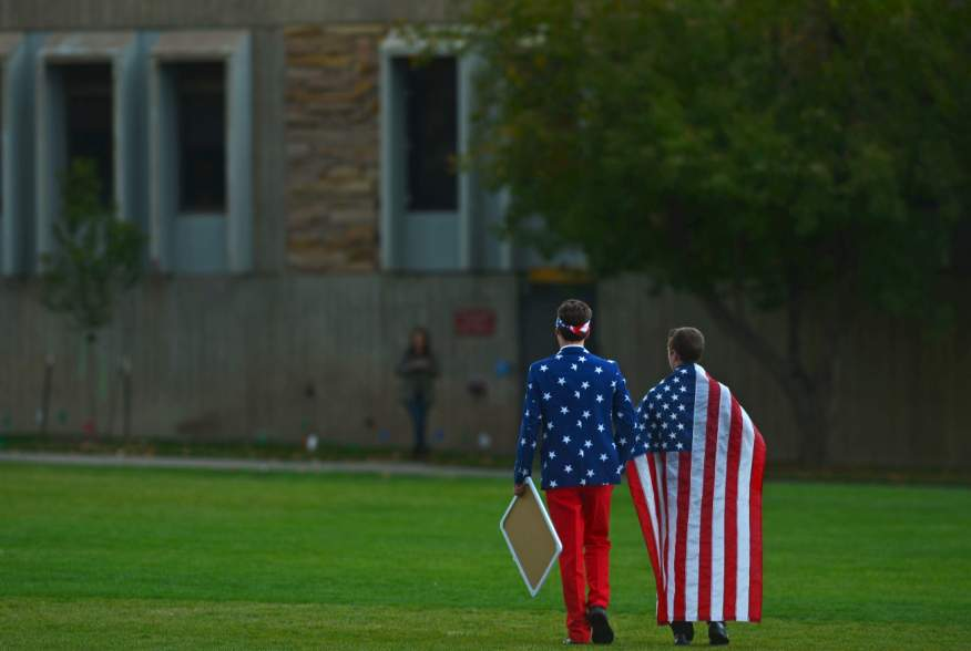 """People wear the American flag as students and protesters gather at the """"Free Speech Zone"""" located at the University of Colorado's Business Field, while candidates gather across the street for a forum held by CNBC, before the U.S. Republican presidential c"""