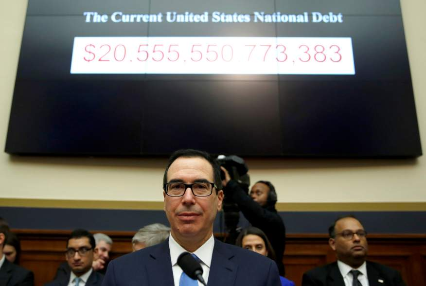 """Treasury Secretary Steven Mnuchin sits under a display of the U.S. national debt as he testifies to the House Financial Services Committee on """"The Annual Report of the Financial Stability Oversight Council"""" on Capitol Hill in Washington, U.S., February 6,"""
