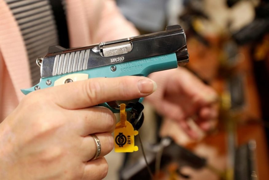 A woman looks over a semi-automatic handgun Kimber Micro Bel Air, a .380 ACP caliber, during the SHOT (Shooting, Hunting, Outdoor Trade) Show in Las Vegas, Nevada, U.S., January 22, 2019. Picture taken January 22, 2019. REUTERS/Steve Marcus