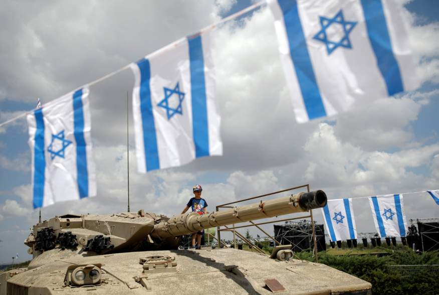 A boy stands atop an old tank during Memorial Day ceremony at Latrun's armoured corps memorial site, Israel May 8, 2019. REUTERS/Corinna Kern