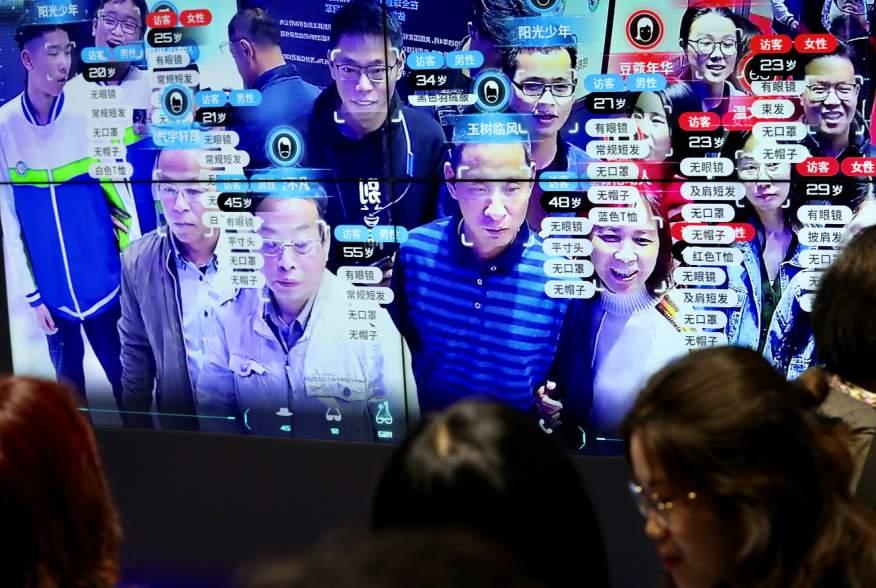 Visitors are seen at a screen displaying facial recognition technology at the Digital China Exhibition in Fuzhou, Fujian province, China May 8, 2019. China Daily via REUTERS