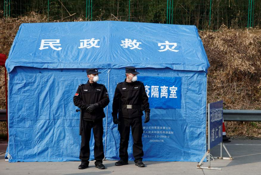Security personnel stand in front of a disaster relief tent at a checkpoint in Yunxi county, Hunan province, near the border to Hubei province, on virtual lockdown after an outbreak of a new coronavirus, in China, January 28, 2020. REUTERS/Thomas Peter
