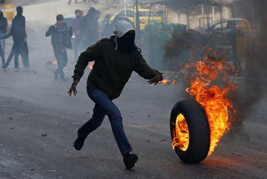 A Palestinian demonstrator rolls a burning tire during a protest against the U.S. President Donald Trump's Middle East peace plan, in Hebron in the Israeli-occupied West Bank January 31, 2020. REUTERS/Mussa Qawasma