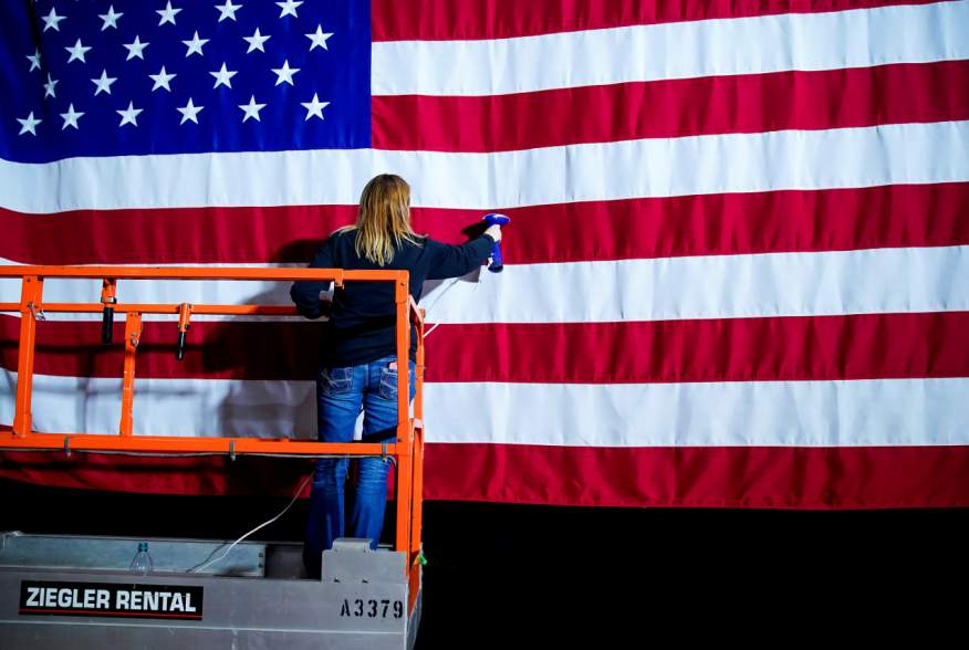 A woman takes the wrinkles from a flag before Pete Buttigieg, Democratic presidential candidate and former South Bend, Indiana mayor attends a watch party on Caucus Day in Des Moines, Iowa, U.S., February 3, 2020. REUTERS/Eric Thayer