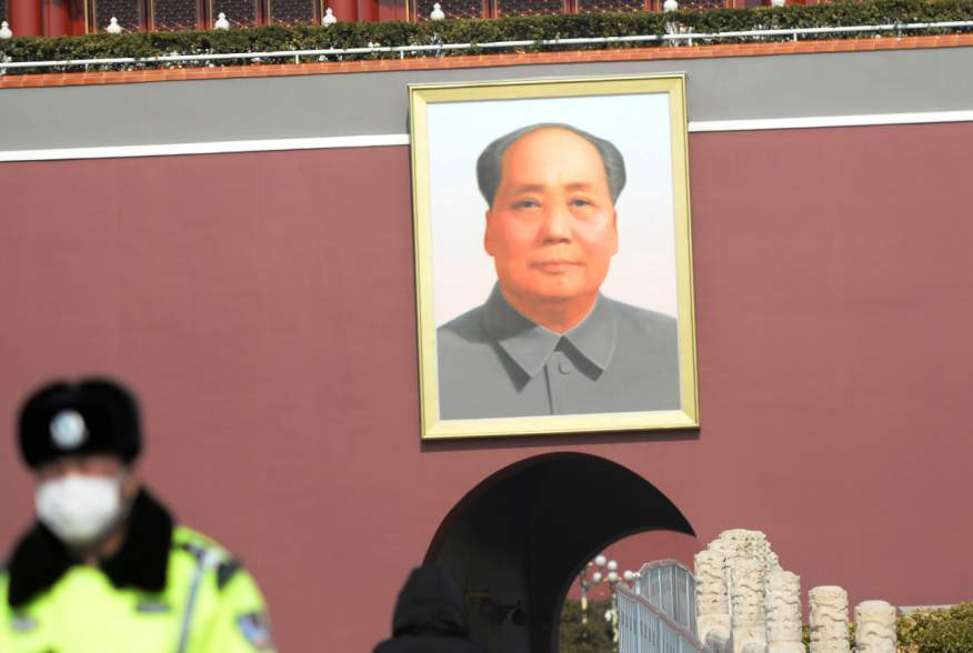 A police officer wearing a face mask stands guard under a giant portrait of the late Chinese chairman Mao Zedong at the Tiananmen Gate as the country is hit by an outbreak of the novel coronavirus, in Beijing, China February 19, 2020. REUTERS/Tingshu Wang