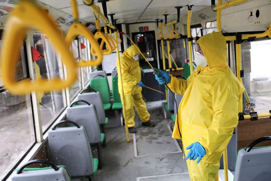 Employees wearing protective gear spray disinfectant to sanitize a passenger bus as a preventive measure against the coronavirus in Lviv, Ukraine March 3, 2020. REUTERS/Mykola Tys