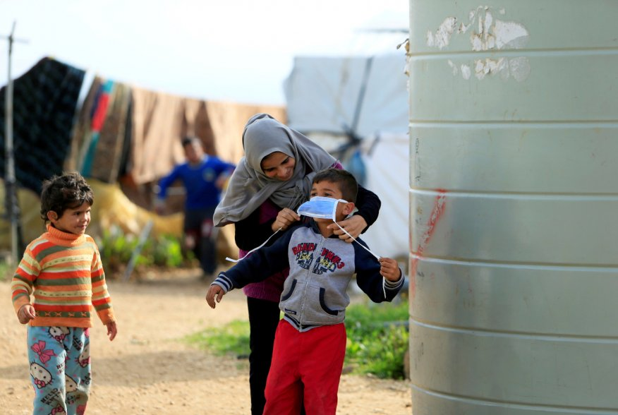 A Syrian refugee woman puts a face mask on a boy as a precaution against the spread of coronavirus, in al-Wazzani area, in southern Lebanon, March 14, 2020. REUTERS/Ali Hashisho