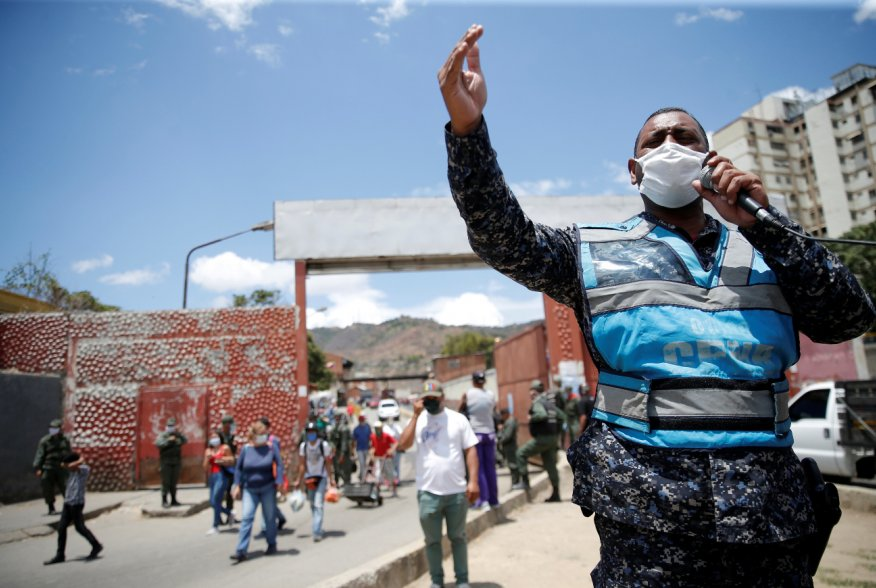 A member of the Bolivarian national police at the gates of a public market asks people to return to their homes during the national quarantine in response to the spread of coronavirus disease (COVID-19) in Caracas, Venezuela, March 21, 2020. REUTERS/Manau