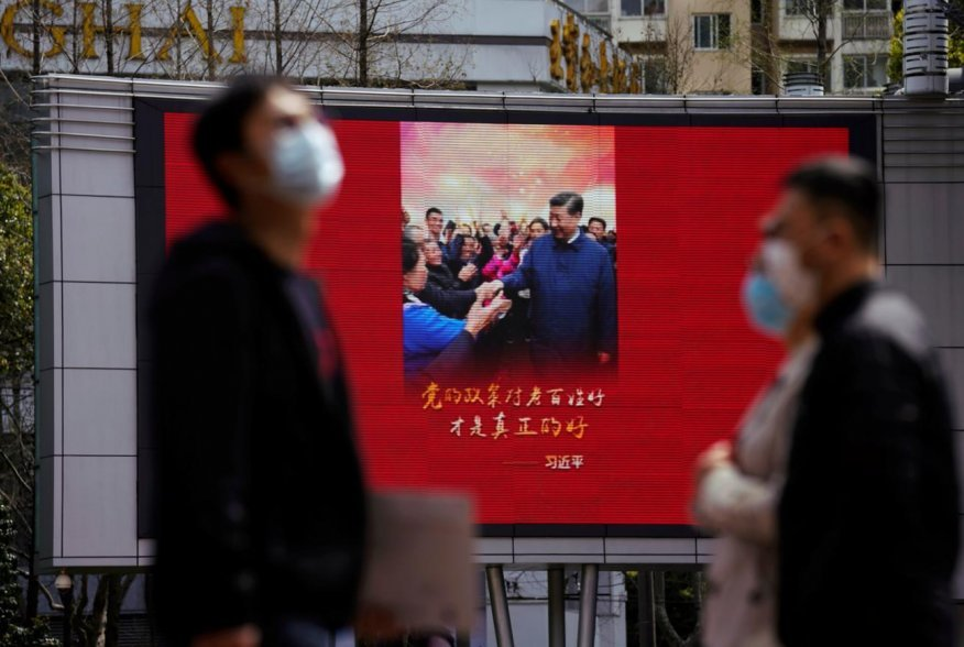 Pedestrians wearing face masks walk past a screen displaying an image of Chinese President Xi Jinping after the city's emergency alert level for coronavirus disease (COVID-19) was downgraded, in Shanghai, China March 23, 2020. REUTERS/Aly Song