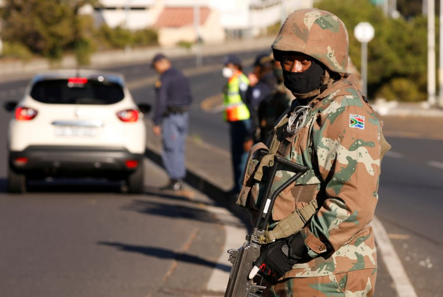 A soldier stands guard as he is joined by police officers to check vehicles as a 21-day lockdown aimed at limiting the spread of coronavirus disease (COVID-19) takes effect in Cape Town, South Africa, March 27,2020.REUTERS/Mike Hutchings