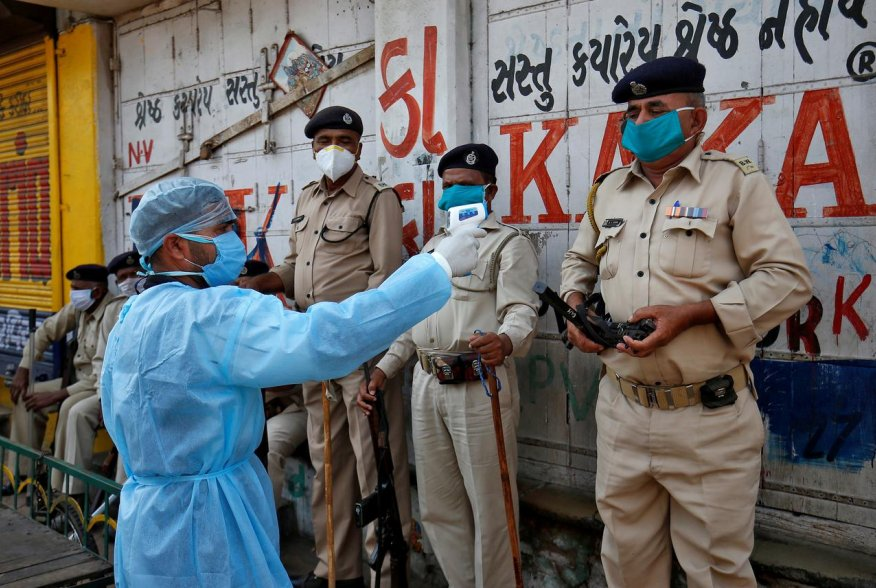 A paramedic uses an infrared thermometer to measure the temperature of a police officer alongside a road during a 21-day nationwide lockdown to slow the spreading of coronavirus disease (COVID-19) in Ahmedabad, India, April 9, 2020. REUTERS/Amit Dave