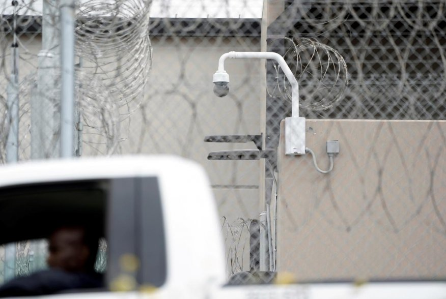 A prison employee drives past a surveillance camera on the grounds of the Otay Mesa Detention Center, a ICE (Immigrations & Customs Enforcement) federal detention center privately owned and operated by prison contractor CoreCivic, amid the coronavirus dis