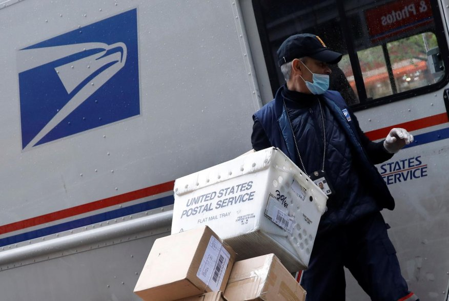 A United States Postal Service (USPS) worker unloads packages from his truck in Manhattan during the outbreak of the coronavirus disease (COVID-19) in New York City, New York, U.S., April 13, 2020. REUTERS/Mike Segar