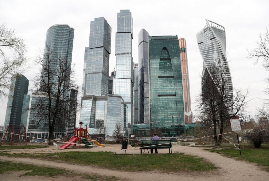 """A woman and a dog are seen on a taped-off playground in front of the Moscow International Business Centre, also known as """"Moskva-City"""", amid the outbreak of the coronavirus disease (COVID-19) in Moscow, Russia April 27, 2020. REUTERS/Evgenia Novozhenina"""