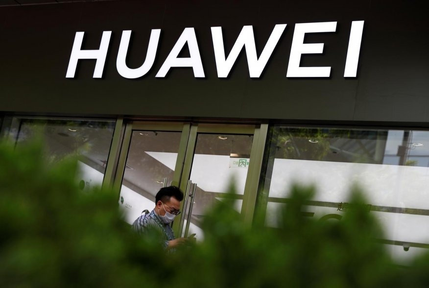 A man in a face mask walks past a Huawei shop, amid an outbreak of the coronavirus disease (COVID-19), in Beijing, China, May 18, 2020. REUTERS/Thomas Peter
