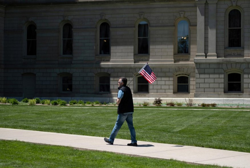 "A man walks with an American flag during ""Operation Haircut"", a protest put on by supporters of the Michigan Conservative Coalition at the state capitol, after barber Karl Manke had his license suspended for violating the coronavirus disease (COVID-19) re"