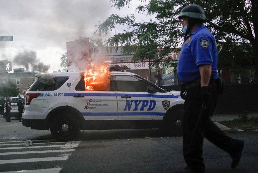 A NYPD police car is sets on fire as protesters clash with police during a march against the death in Minneapolis police custody of George Floyd, in the Brooklyn borough of New York City, U.S., May 30, 2020. REUTERS/Eduardo Munoz