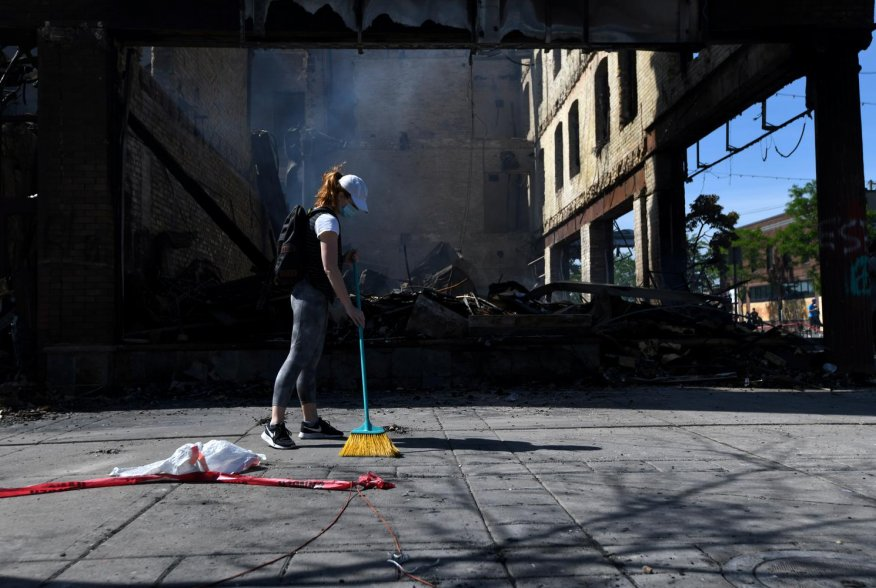 Minneapolis resident, Andrea Stoesz, cleans up outside the burned out bar Nuevo Rodeo across from the Minneapolis Police fifth precinct after the death in police custody of George Floyd in Minneapolis, Minnesota, U.S. May 31, 2020. REUTERS/Nicholas Pfosi
