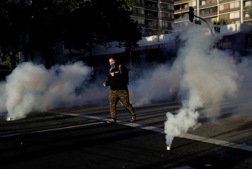 A demonstrator runs after police fired tear gas during a rally amid nationwide unrest following the death in Minneapolis police custody of George Floyd, in Oakland, California, U.S., June 1, 2020. REUTERS/Stephen Lam