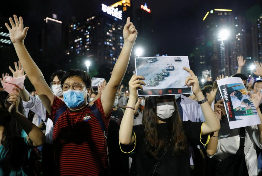 Protesters wearing protective face masks take part in a candlelight vigil to mark the 31st anniversary of the crackdown of pro-democracy protests at Beijing's Tiananmen Square in 1989, after police rejects a mass annual vigil on public health grounds, at