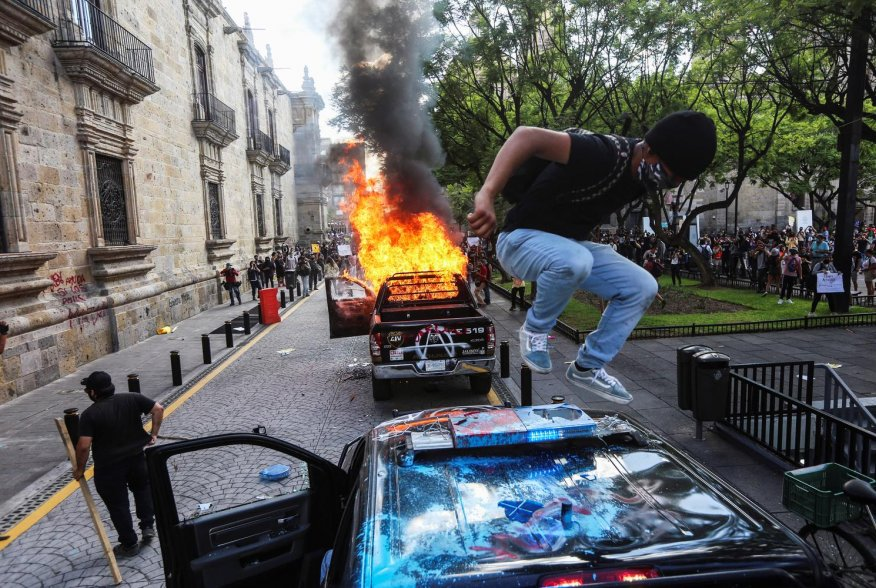 A demonstrator jumps on a damaged police vehicle after demonstrators set it on fire during a protest to demand justice for Giovanni Lopez, a construction worker who died after being arrested for not wearing a face mask in public, during the coronavirus di