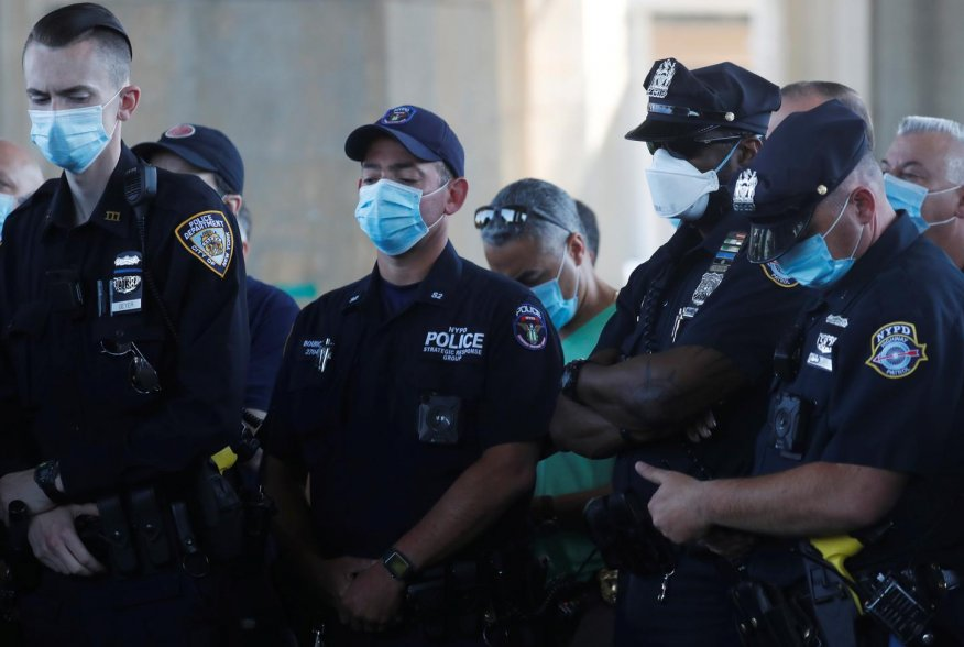 Uniformed officers wear protective face masks as they listen while Police Benevolent Association of the City of New York President Pat Lynch speaks as he and representatives from other New York City Police Department (NYPD) and law enforcement unions hold