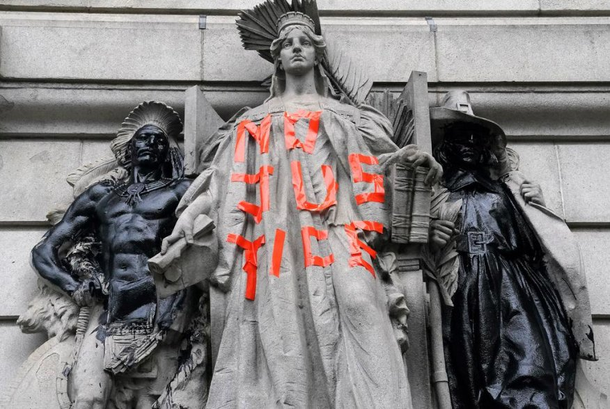 """A defaced statue is pictured across from a protest to defund the police in a place they are calling the """"City Hall Autonomous Zone"""" in support of """"Black Lives Matter"""" in the Manhattan borough of New York City, New York, U.S., June 30, 2020. REUTERS/Carlo"""