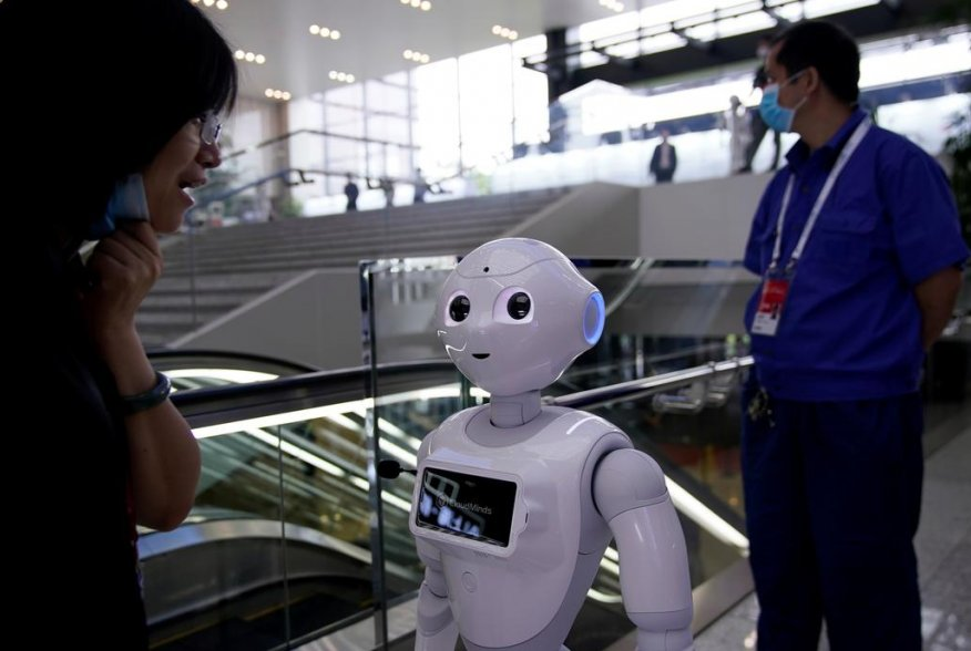 People wearing face masks following the coronavirus disease (COVID-19) outbreak are seen near a robot at the venue for the World Artificial Intelligence Conference (WAIC) in Shanghai, China July 9, 2020. REUTERS/Aly Song