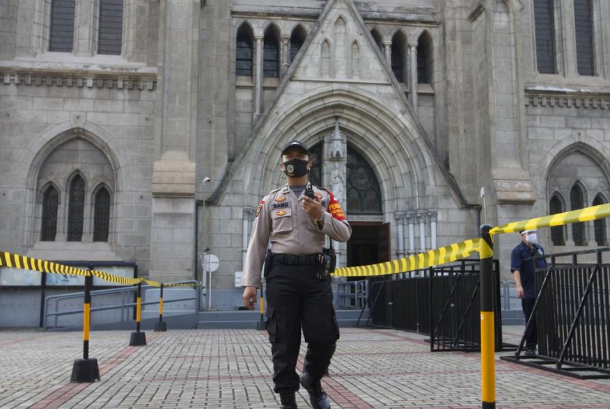 A policeman, part of a large-scale task force enforcing social restrictions amid the coronavirus disease (COVID-19) outbreak, walks with a face mask outside a church on the first day of its reopening, in Jakarta, Indonesia, July 12, 2020. REUTERS/Ajeng Di