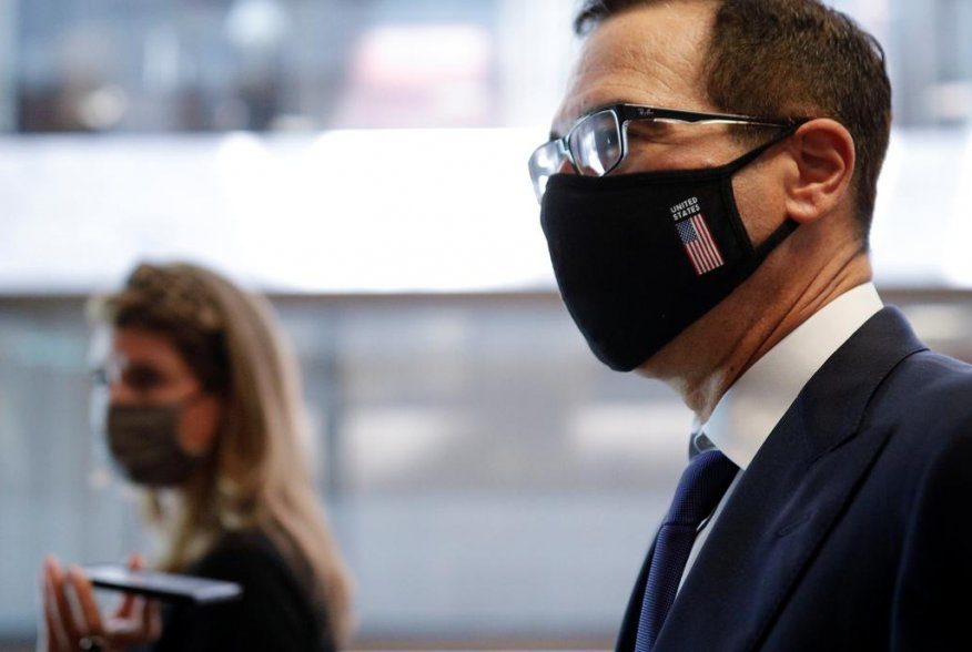 U.S. Treasury Secretary Steve Mnuchin, wearing a face mask, walks with news reporters, following a series of meetings with members of Congress on Capitol Hill in Washington, U.S. July 21, 2020. REUTERS/Tom Brenner