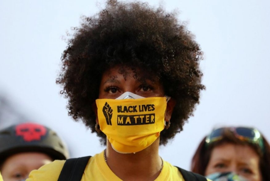 """A protester with the """"Black Lives Matter"""" slogan printed on her face mask joins a protest against racial inequality and police violence in Portland, Oregon, U.S., July 26, 2020. REUTERS/Caitlin Ochs"""