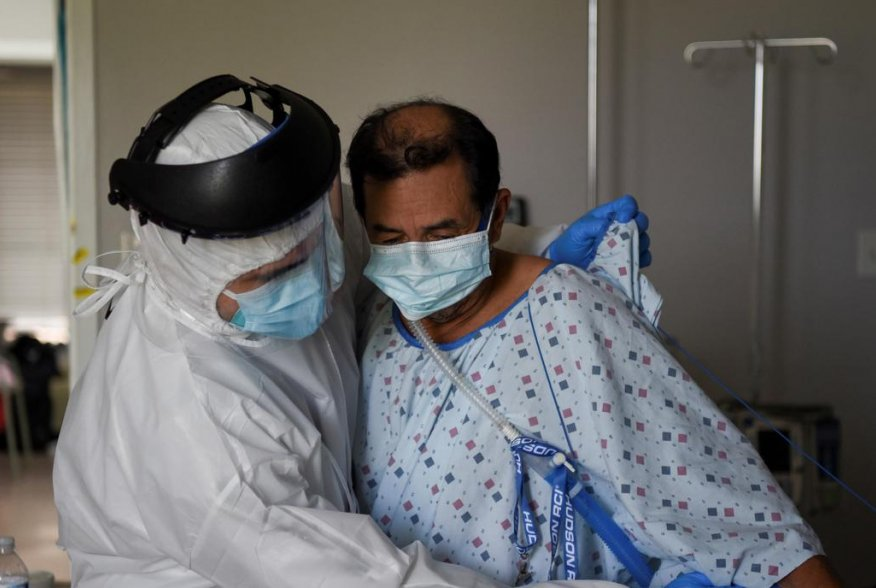 Fernando Olvera, 26, a medical school student, helps Efrain Guevara, 63, who has been hospitalised with COVID-19, get up from his hospital bed, at United Memorial Medical Center (UMMC), during the coronavirus disease (COVID-19) outbreak, in Houston, Texas