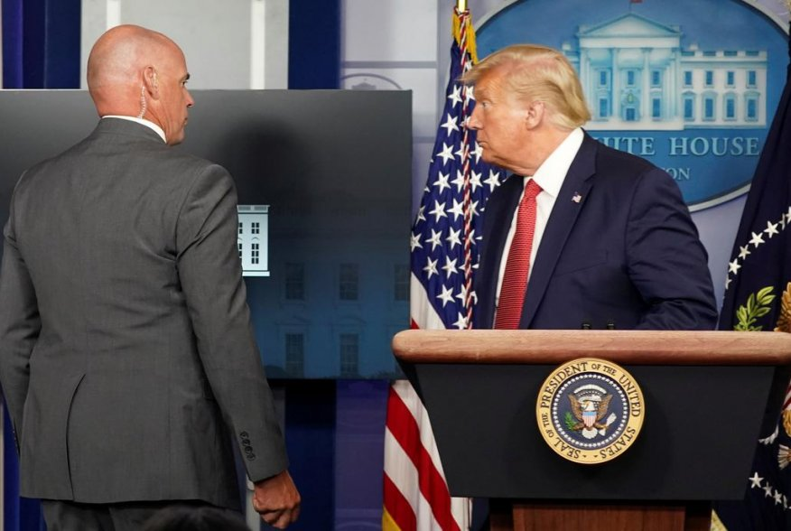 A Secret Service agent escorts U.S. President Donald Trump from a coronavirus disease (COVID-19) pandemic briefing after a shooting outside the White House in Washington, U.S., August 10, 2020. REUTERS/Kevin Lamarque