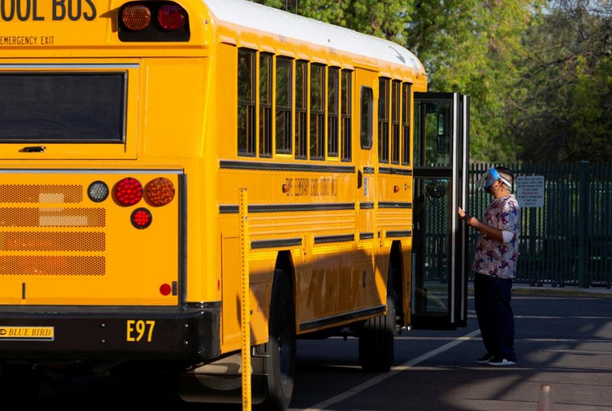 An employee waits to assist a student off a bus as in-person learning resumes with restrictions in place to prevent the spread of coronavirus disease (COVID-19) at Rover Elementary School in Tempe, Arizona, U.S., August 17, 2020. REUTERS/Cheney Orr