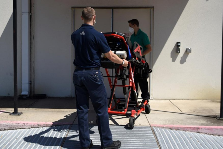 Orion EMS employees wheel a stretcher into the Houston Methodist Emergency Care Center at Kirby while wearing protective equipment to prevent the spread of the coronavirus disease (COVID-19) in Houston, Texas, U.S., August 19, 2020. REUTERS/Callaghan O'Ha