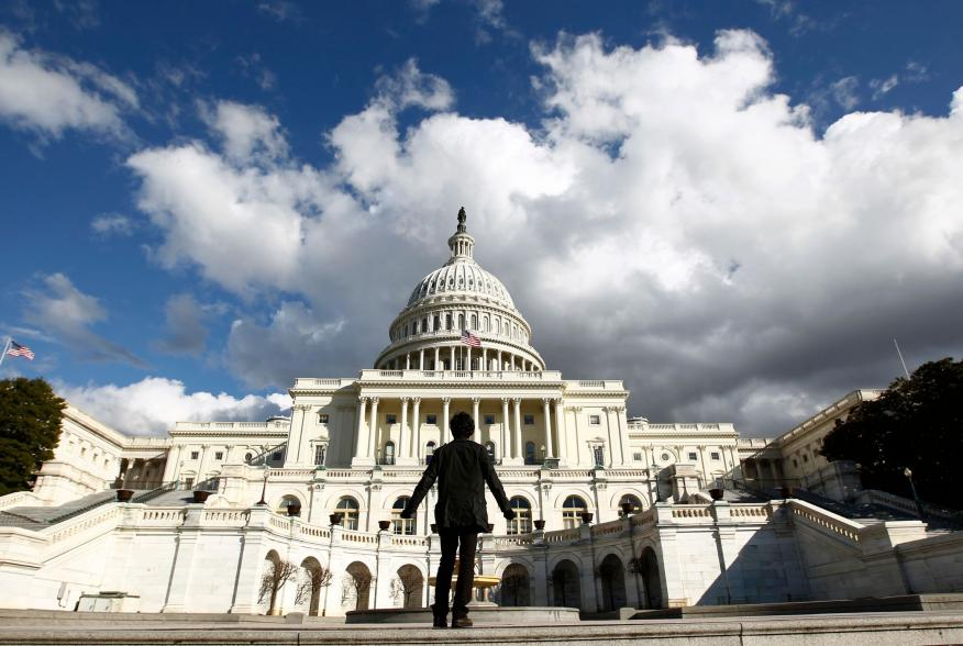 A tourist gazes up towards the dome of the U.S. Capitol in Washington January 25, 2010. On Wednesday, U.S. President Barack Obama will deliver his first State of the Union speech in the House Chamber of the Capitol. REUTERS/Kevin Lamarque (UNITED STATES -