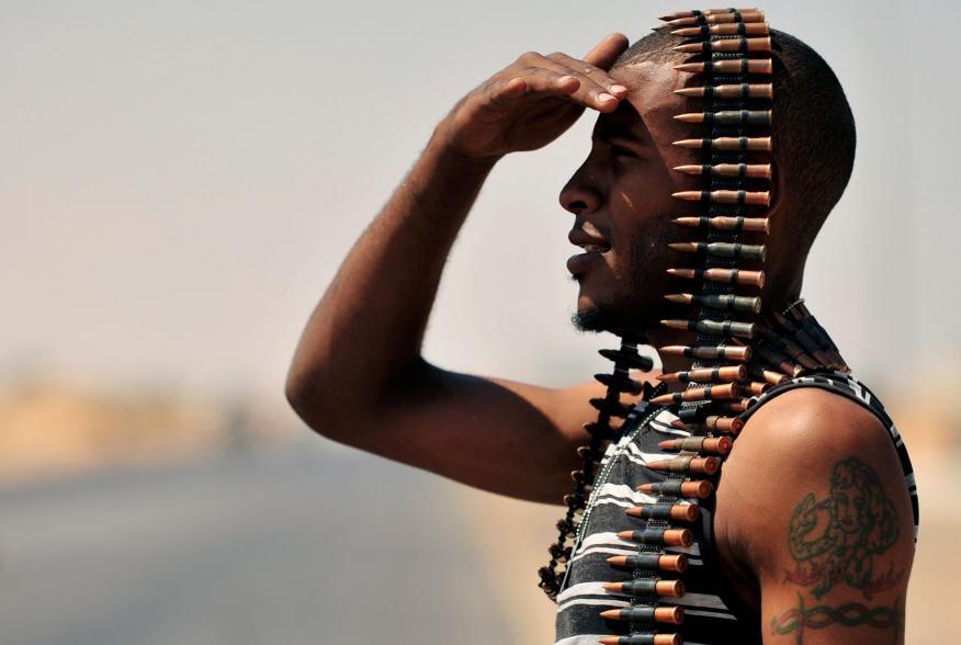 A Libyan rebel stands guard near the entrance of Ras Lanuf August 27, 2011. REUTERS/Esam Al-Fetori (LIBYA - Tags: POLITICS CIVIL UNREST TPX IMAGES OF THE DAY CONFLICT)