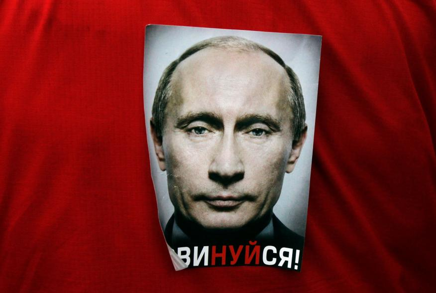 """A participant wears a sticker with the word """"Obey!"""" during an opposition protest on Revolution square in central Moscow February 26, 2012. Thousands of Russians joined hands to form a ring around Moscow city centre on Sunday in protest against Vladimir Pu"""