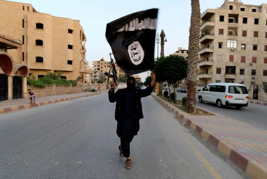 """A member loyal to the Islamic State in Iraq and the Levant (ISIL) waves an ISIL flag in Raqqa June 29, 2014. The offshoot of al Qaeda which has captured swathes of territory in Iraq and Syria has declared itself an Islamic """"Caliphate"""" and called on factio"""