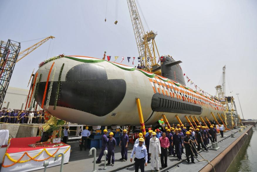 Employees stand around the Indian Navy's first Scorpene submarine before being undocked from Mazagon Docks Ltd, a naval vessel ship building yard, in Mumbai April 6, 2015. Irked by India's status as the world's biggest arms importer, Prime Minister Narend