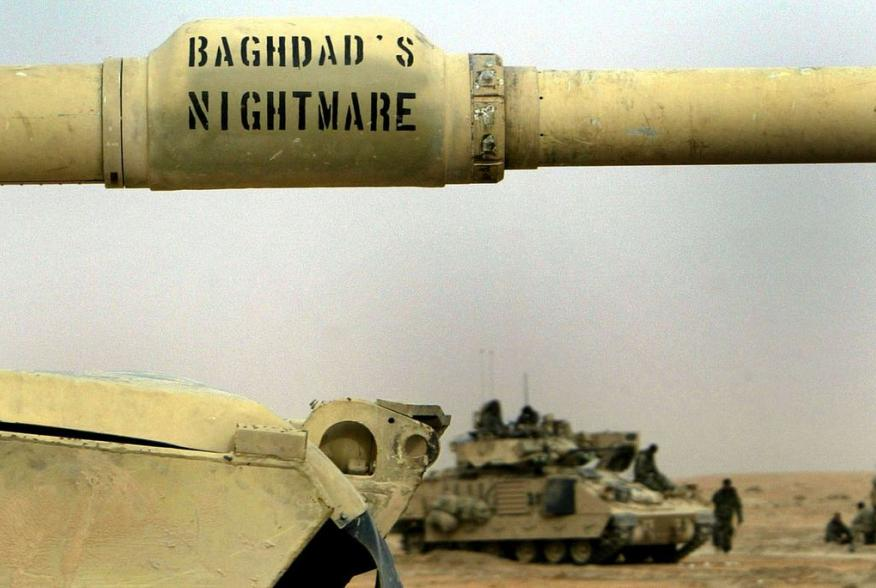"A US Army 3rd Infantry M1A1 Abrams tank with ""Baghdad's nightmare"" written on its cannon passes Infantry troops relaxing near the Euphrates river as hundreds of armored vehicles push towards the outskirts of Baghdad early April 6, 2003. More and more US f"