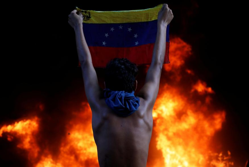 A protester holds a national flag as a bank branch, housed in the magistracy of the Supreme Court of Justice, burns during a rally against Venezuela's President Nicolas Maduro, in Caracas, Venezuela June 12, 2017. REUTERS/Carlos Garcia Rawlins TPX IMAGES