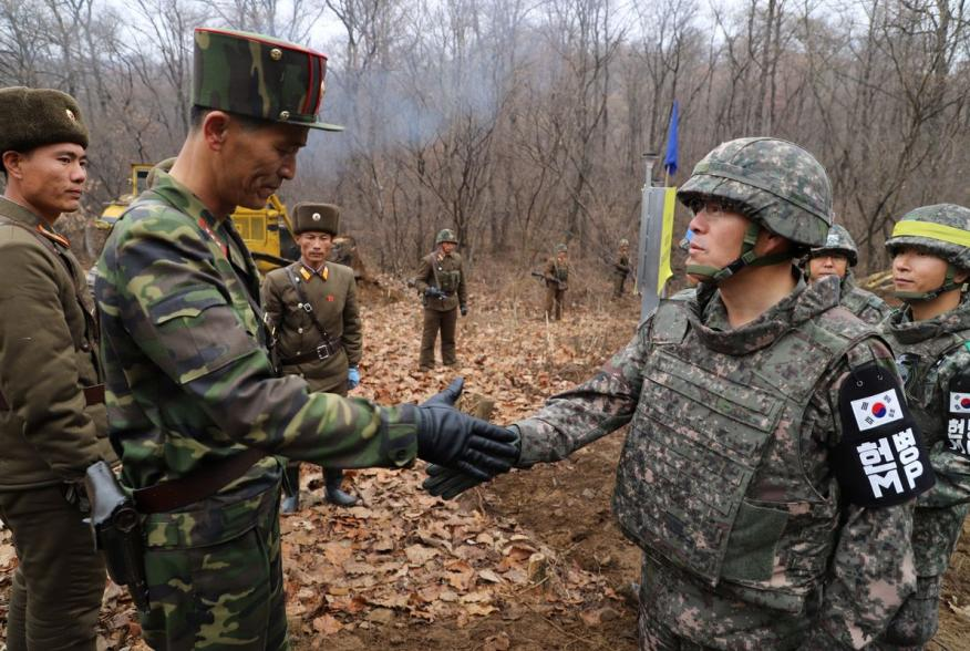 A South Korean military officer (R) and a North Korean military officer shake hands during an operation to reconnect a road across the Military Demarcation Line inside the Demilitarised Zone (DMZ) separating the two Koreas November 22, 2018. Picture taken