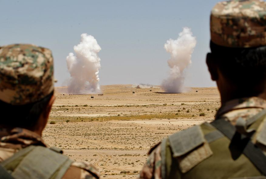 """Jordanian soldiers watch smoke rising during an artillery drill, part of the """"Eager Lion"""" military exercise near the southern town of Al Quweira, 50 km (30 miles) from the coastal city of Aqaba, June 19, 2013. Eager Lion military exercise, set to take pla"""