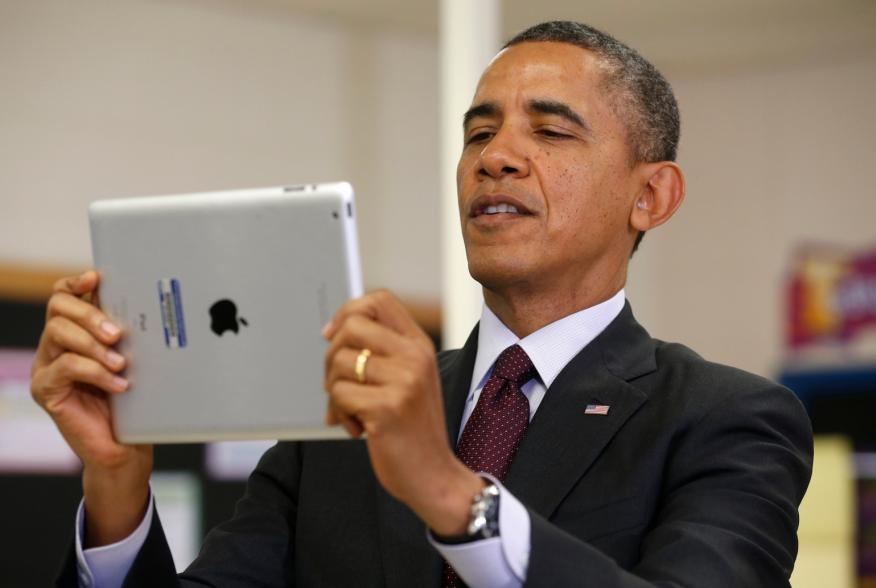 U.S. President Barack Obama holds up an Apple iPad during a visit to Buck Lodge Middle School in Adelphi, Maryland February 4, 2014.